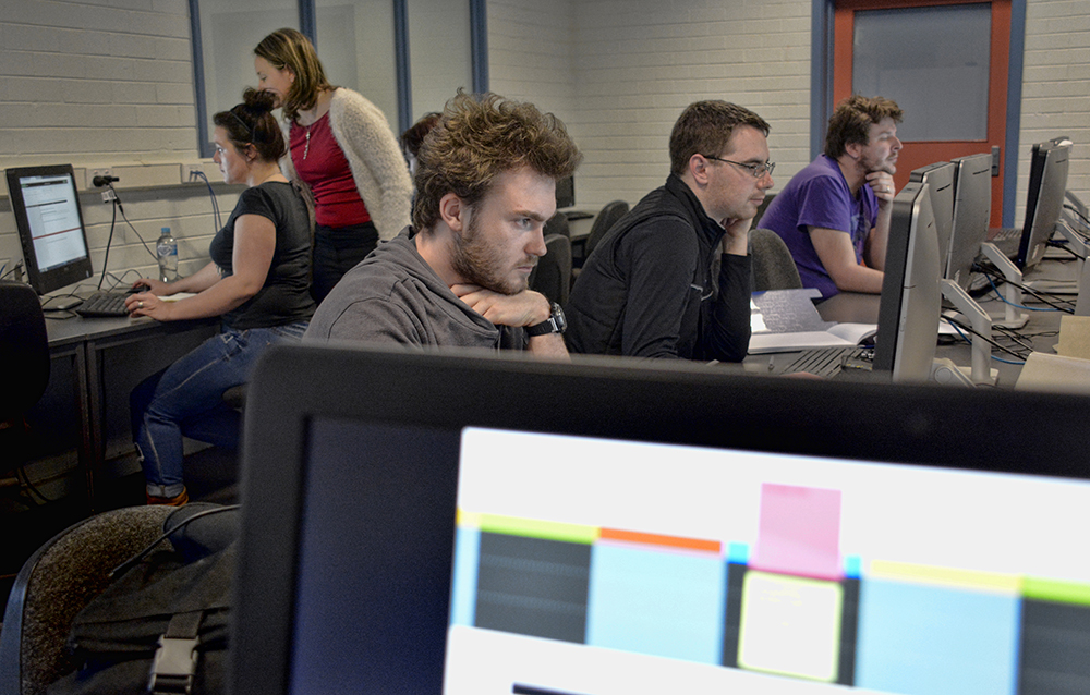 L to R Jack Walsh, Shannon Carter and Lewis Adams concentrate on editing Painted Words Submissions while Emma Burgess-Gilchrist confer in the background.